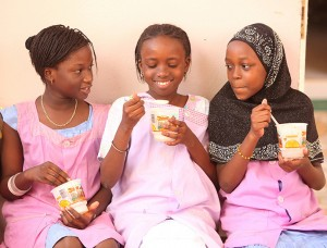 The World Bank finds that when a girl completes her primary education, she will earn more over her lifetime. These young girls are taking part of a school feeding program in the commune of Mbao, near Dakar, Senegal..