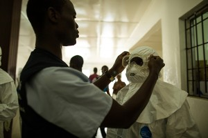 Health care workers put on personal protective equipment before going into the hot zone at the Island Clinic in Monrovia
