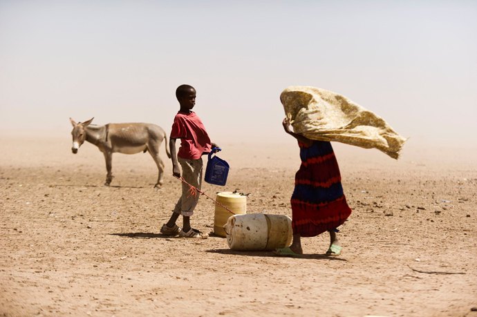 A boy and a woman struggle with the dusty wind looking for water in Wajir, Kenya