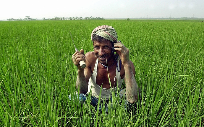 Bangladeshi farmer Jalal Kha talks over a mobile phone as he works in his paddy field. / AFP, Farjana K. Godhuly