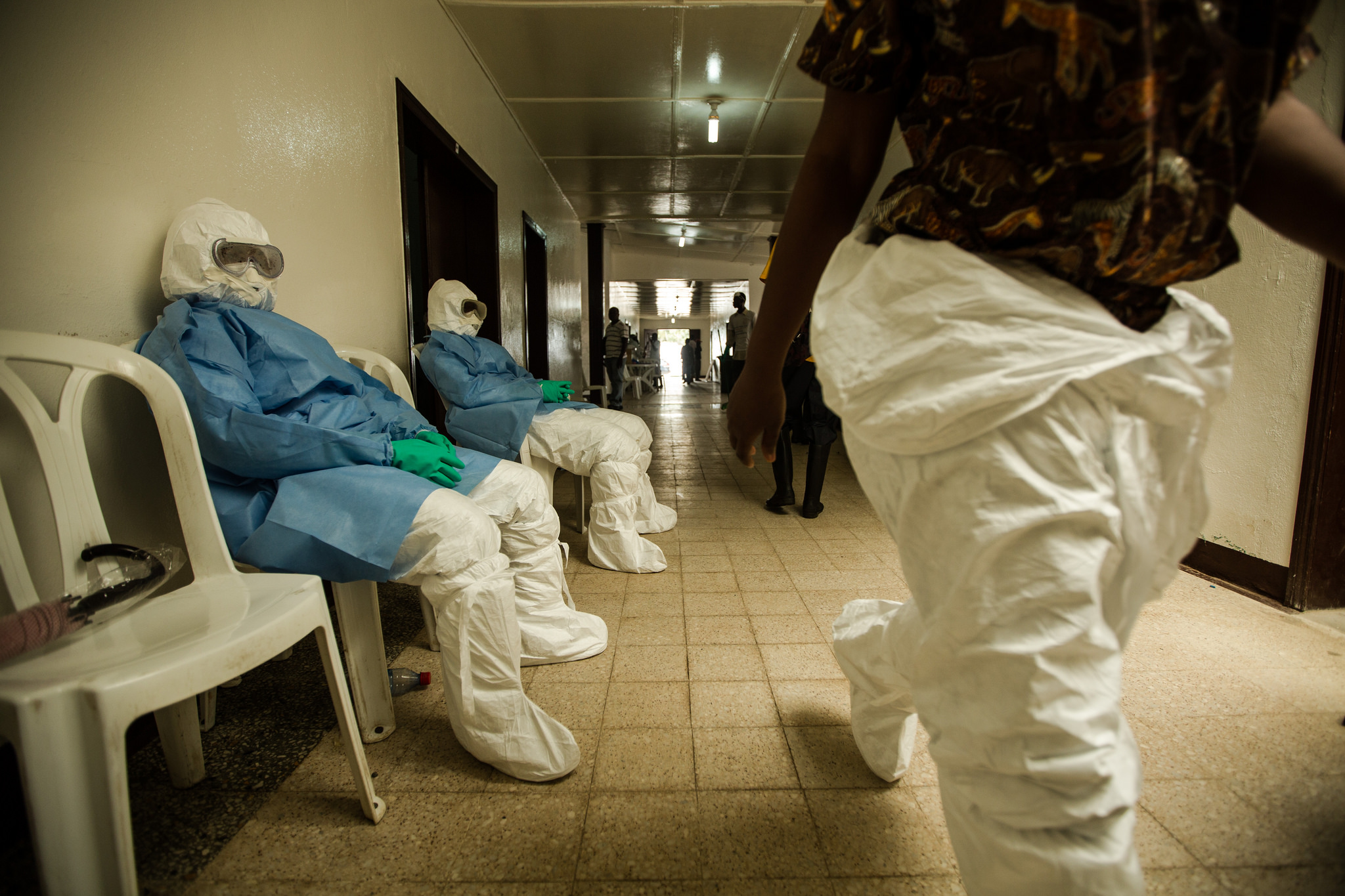 Health workers in personal protective equipment (PPE) wait to enter the hot zone at Island Clinic / Morgana Wingard
