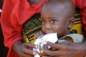 A child eats his ready-to-use therapeutic food to treat his malnutrition. / USAID, Katie McKenna