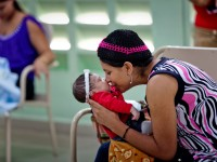 A mother plays with her child while waiting for services at Jose Maria Cabral y Baez Hospital in Santiago, Dominican Republic. Health workers and supervisors from this hospital participated in a workshop and supportive site supervision system designed and delivered by the Directorate of STI/HIV/AIDS (DIGECITSS), the health services network (REDES), and CapacityPlus to improve the quality of services to eliminate mother-to-child transmission of HIV and congenital syphilis. / Wendy Tactuk, courtesy of CapacityPlus and IntraHealth International