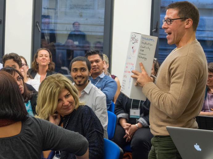 """Workshop participant Josh Machleder of Internews uses a creative prop during the """"product in a box"""" exercise explaining how to nurture civil society activism under restrictive conditions. / Reboot"""