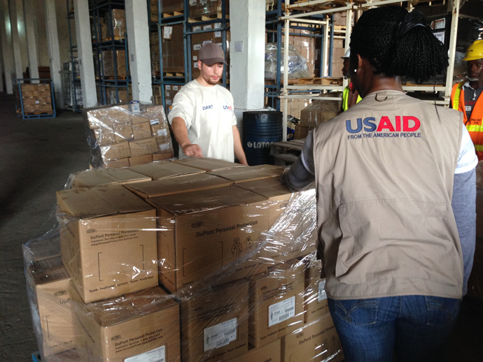 "Inside a warehouse in Monrovia, the U.S. military and USAID put together ""starter kits"" of medical and cleaning supplies to sustain U.S.-supported Ebola clinics for the first critical days of operation. / Carol Han, USAID/OFDA"