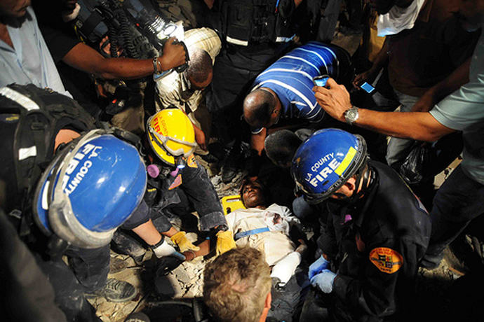 Members of the Los Angeles County Fire Department Search and Rescue Team rescue a Haitian woman from a collapsed building in downtown Port-au-Prince. The woman had been trapped in the building for five days without food or water. / U.S. Navy, Mass Communication Specialist 2nd Class Justin Stumberg