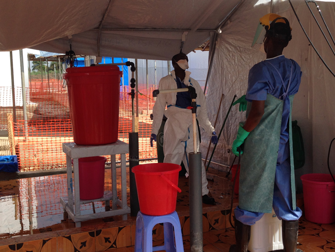 Taking off protective suits—like what's being done here at a USAID-supported ETU in Sierra Leone—is a vulnerable time for health care workers. That's why so much time is spent teaching health care workers how to prevent cross-contamination.  / Carol Han, USAID