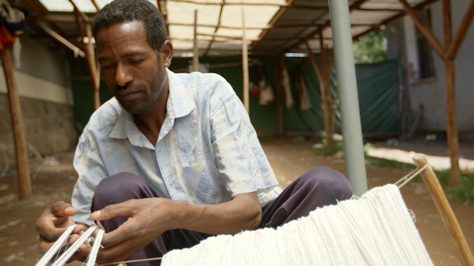A worker at Muya Ethiopia weaves fabric that will become clothing and accessories sold on store shelves thousands of miles away. From 2005 to 2014, with support from USAID, Muya expanded from seven to 400 full-time employees and now sells 90 percent of its products overseas. / IESC, Steve Dorst
