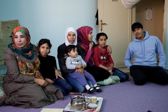 A Syrian family in Mafraq, Jordan takes a moment at the end of a school day to discuss their challenges and aspirations. / Peter Bussian, USAID