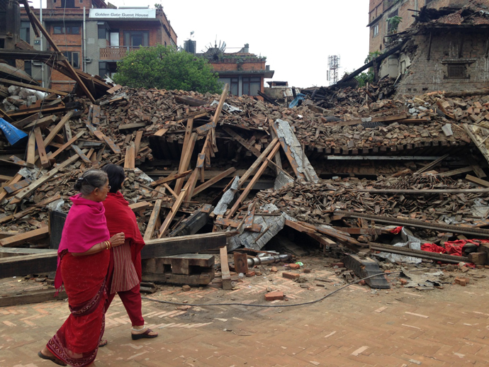 Days after Saturday's earthquake, women look on at the destruction in hard-hit Bhaktapur. / Natalie Hawwa, USAID
