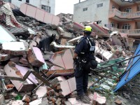 A member of USAID's Disaster Assistance Response Team -- from Fairfax County's urban search-and-rescue team -- works with a canine to search for survivors in the rubble of a collapsed building in Bhaktapur, Nepal. / Fairfax County Fire and Rescue