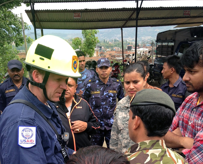 Mike Davis, a member of USAID's Disaster Assistance Response Team, speaks with the Nepalese Army and the community in Bhaktapur, Nepal to figure out where people may be trapped. / Natalie Hawwa, USAID