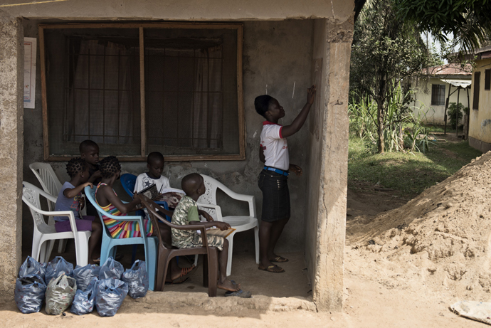 While schools were closed due to Ebola, Aminata, 16, and her siblings refused to put learning on hold. With the help of her mother, Aminata led classes for the family and several neighborhood children. Now, schools have safely reopened and the kids are happy to be back. / Neil Brandvold, USAID