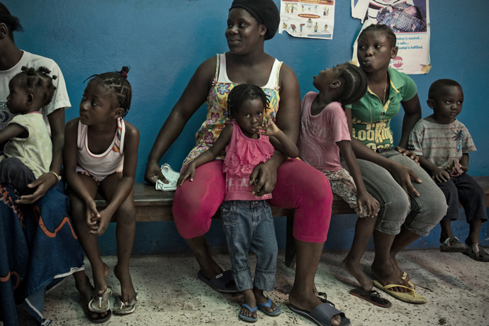 Mothers and their children wait to be seen for primary health care services at the USAID-supported Star of the Sea Clinic in Monrovia, Liberia. / Neil Brandvold, USAID