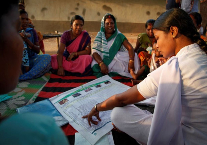 "Community members in a village in eastern India learn about the ""My Village My Home"" tool at a vaccination session. / MCHIP"