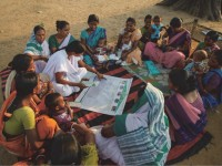 "Esther Das, an auxiliary nurse midwife, reviews the ""My Village My Home"" tool with community members in a village in Eastern India. / MCHIP"