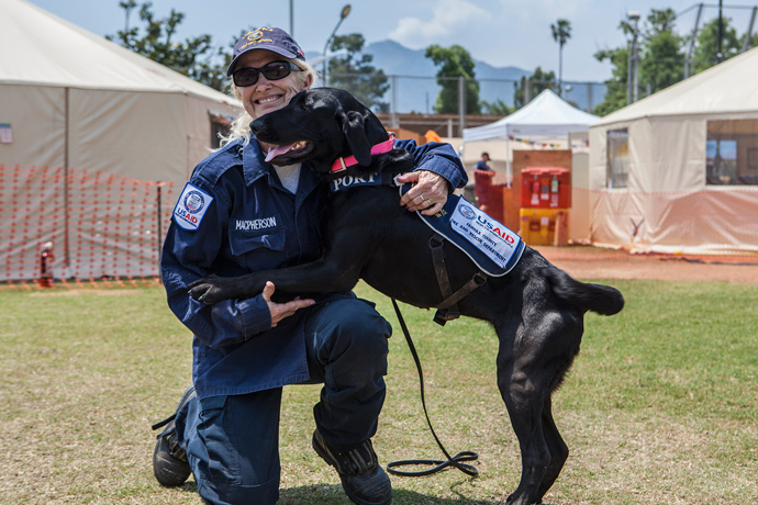 Teresa MacPherson of Catlett, Va., with canine responder Port in Nepal. / Kahish Das Shrestha for USAID