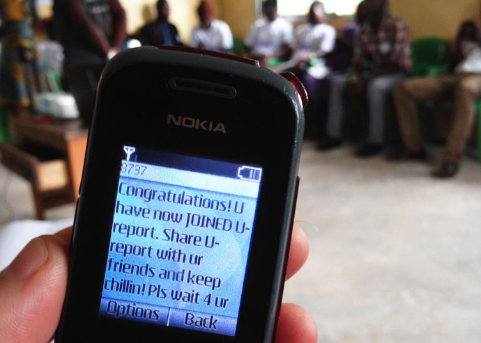 Youth-turned-social mobilizers in Liberia learn how to use social media tools on their cell phones to stay connected while spreading awareness about Ebola prevention in communities. / Eric King, USAID