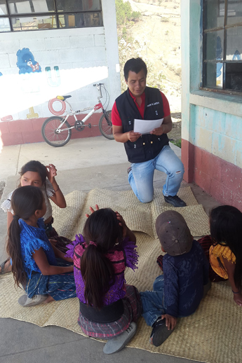 Andrés Ixcuná Mateo, a community volunteer with the Leer Juntos, Aprender Juntos project, helps children learn to read in San Andrés Sajcabajá, Guatemala. / Save the Children
