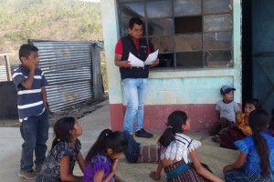 Andrés Ixcuná Mateo, a community volunteer with the Leer Juntos, Aprender Juntos project, helps children learn to read in San Andrés Sajcabajá, Guatemala. / Save the Children