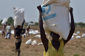 A woman carries a sack of food aid after a food drop in a field in Nyal, near South Sudan's border with Sudan. USAID is the largest donor to the UN World Food Program in South Sudan. / Tony Karumba, AFP