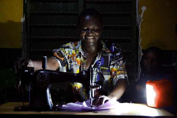Thanks to Power Africa, increasing numbers of Africans can continue working well beyond daylight hours, helping increase their productivity and potential earnings. This Tanzanian man can sew at night thanks to a d.light solar lantern provided through Power Africa. / USAID