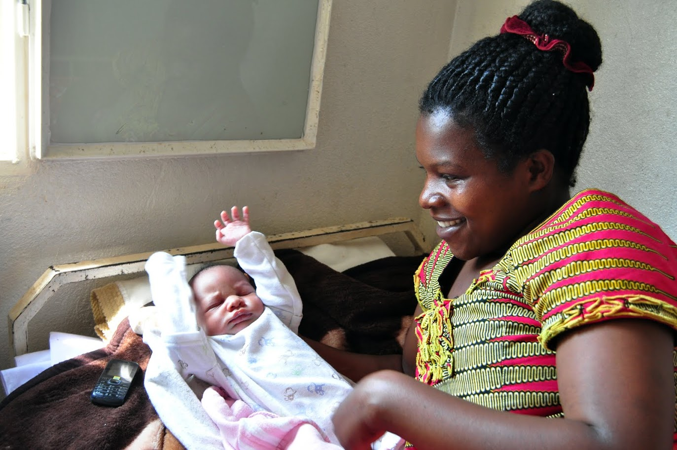 A mother in Rwanda with her ​newborn ​daughter. Investing in survival & health can lead to greater individual and national productivity and growth. / Amy Fowler, USAID