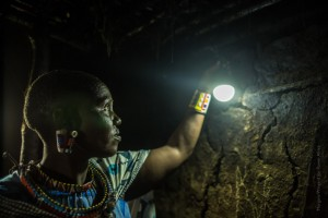 Lucy Sakuda, 47, uses her M-KOPA solar powered light in her home in Olorien, Kenya to cook at night. Before buying a solar panel, the nearest power source was 15 miles away. She has saved so much from not having to buy kerosene that she was able to get new furniture. / Morgana Wingard