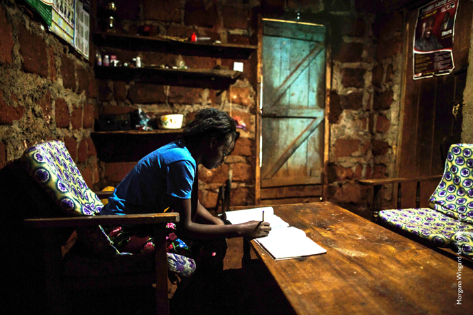 Paris Wanjiru, 17, uses a solar-powered light created by M-Kopa to study at night. Before her home had electricity, she was ranked sixth in her class; now, she ranks second. / Morgana Wingard, USAID