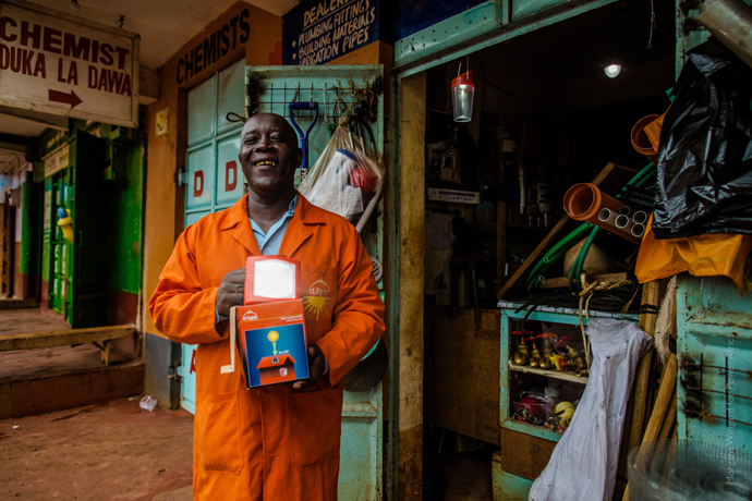 "John Njorge, a ""solar‐preneur,"" sells about 60 d.light solar lamps a month at his shop in the small town of Maragua, Kenya. He also uses the lamps to light the shop so he can stay open later. / Morgana Wingard, USAID"