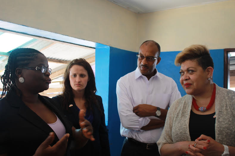 USAID's Senior Ebola Coordinator Denise Rollins (right), Mission Director John Mark Winfield (second from right) and Bureau of Legislative and Public Affairs staffer Kate Alexander listen as a staff member of DuPort Road Clinic in Paynesville, Liberia speaks to them. / Jonta Williams, USAID