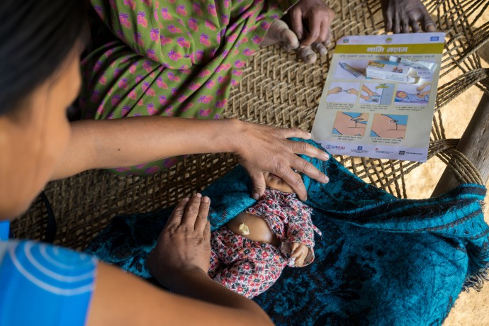 Jharana Kumari Tharu, a female community health volunteer in Nepal, demonstrates how a simple tube of chlorhexidine antiseptic gel could help prevent infection and even death when applied to a baby's cut umbilical cord stump. / Thomas Cristofoletti, USAID