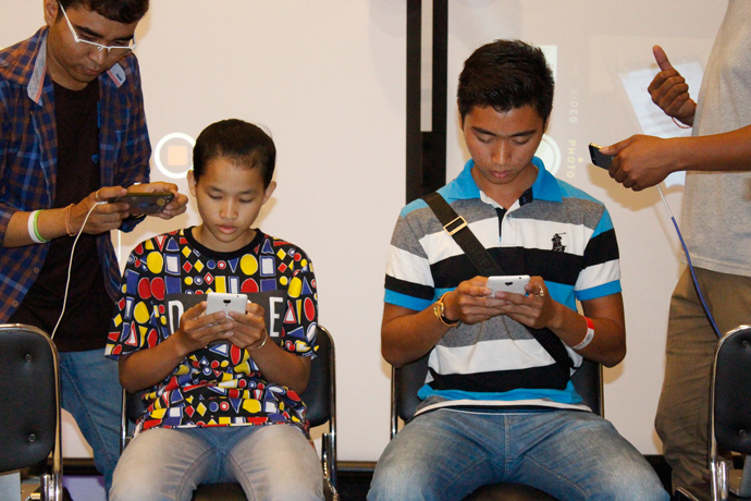 Two boys competed in a mobile phone typing contest in March 2015 to showcase how fast and easy typing in their native language, Khmer, can be with the Khmer Smart Keyboard, an app developed with assistance from Development Innovations. / Chantheng Heng, USAID