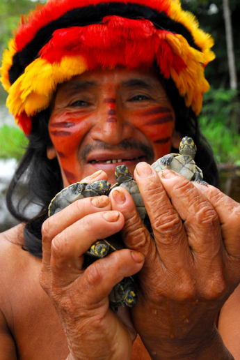 A prominent member of the Huambracocha community in Peru's Pastaza river basin wears a traditional macaw feather cap. USAID engages with indigenous communities like his to ensure wildlife populations -- including macaws and river turtles -- are managed well and available for local use. / Michael Tweddle
