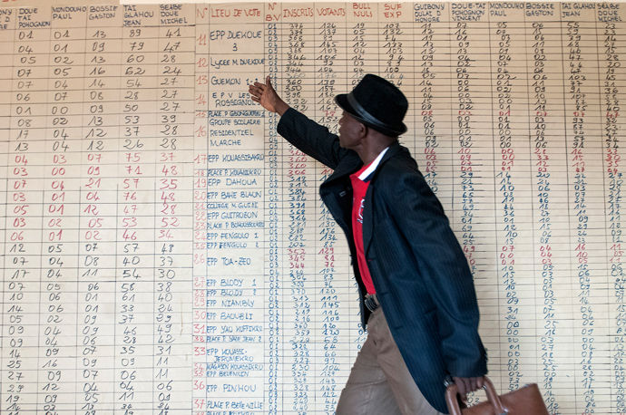 A local elections official in Duékoué, Côte d'Ivoire, explains the tabulation of votes from a previous election. Ahead of next week's presidential election, USAID's Office of Transition Initiatives has implemented activities focused on capacity-building of electoral institutions, improved access to credible information, increased inter-community dialogue, and widespread community mobilization and engagement in the electoral process. / Kendra Helmer, USAID