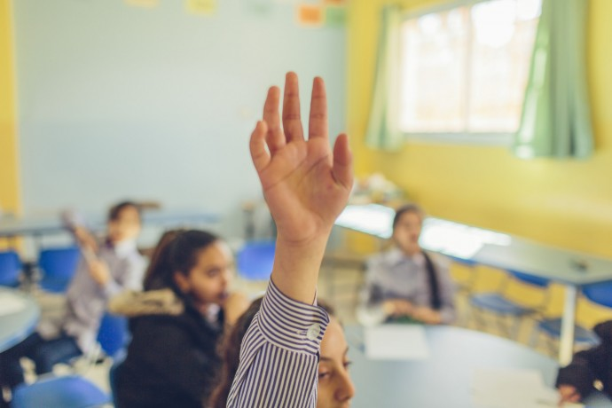 A student at the Saffa Girls School in the West Bank raises her hand in class. The school is one of 57 in the area that USAID provided teacher training to. The school now also has 28 rehabilitated classrooms, a computer and science lab, a library, resource center, and a protected playground. / Bobby Neptune for USAID.