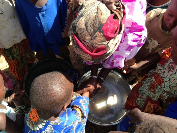 Children watch as a woman and child practice hand washing in Mali. / WASHplus