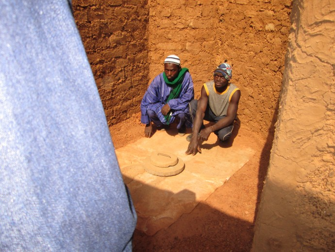 Men show onlookers an open toilet in Mali. / WASHplus