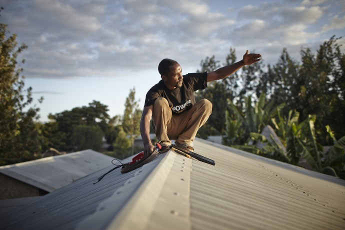 An M-POWER installation agent places a solar panel on a roof in Tanzania. / Mathieu Young, Off.Grid:Electric, for the Power Africa Photo Contest