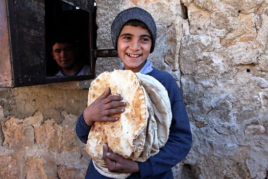 A young boy smiles as he walks out of his local bakery, arms full of freshly baked bread. Families such as this boy's family rely on local bakeries to get their daily bread.