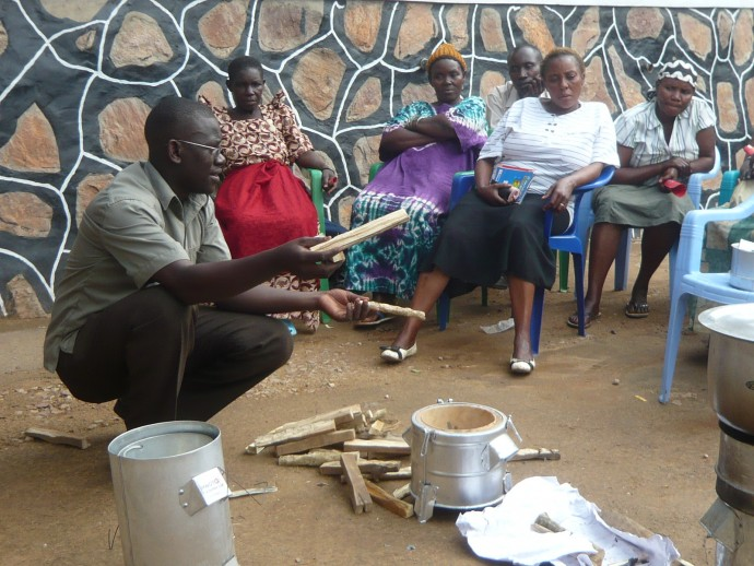A community organizer in Uganda demonstrates the use of the TLUD stove to a local group. / Kendra Williams, URC