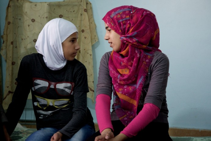 These two Syrian sisters now live as refugees in Mafraq, Jordan. / Peter Bussian for USAID