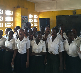 Students at the Lango Lippaye Elementary, Junior and Senior High School in Kakata, Liberia sing to welcome the visitors. / Courtney Babcock, USAID