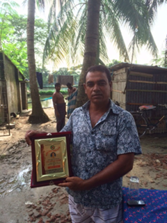 Shahinur Rahman with his award from the local government for the quality of his fish. / Christine Ryan, USAID