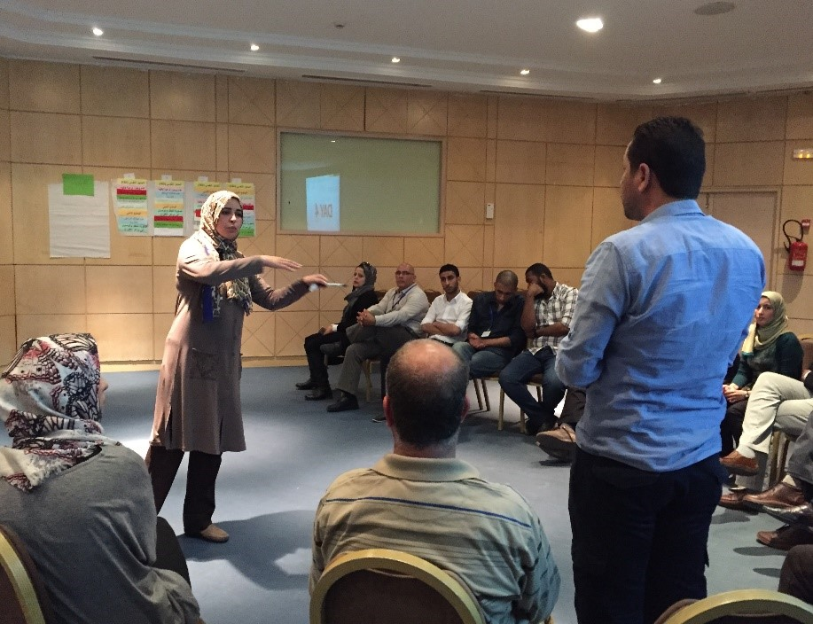 A participant of a gender and elections workshop engages men and women in discussion.