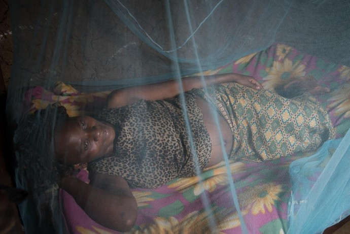 In Kenya, Christine Pepela sleeps under an insecticide-treated bed net provided by a local nurse. / Allan Gichigi, MCSP