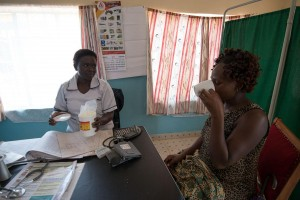 Nurse Agnes Nambuya gives Christine sulfadoxine-pyrimethamine drugs to prevent malaria in pregnancy. / Allan Gichigi, MCSP