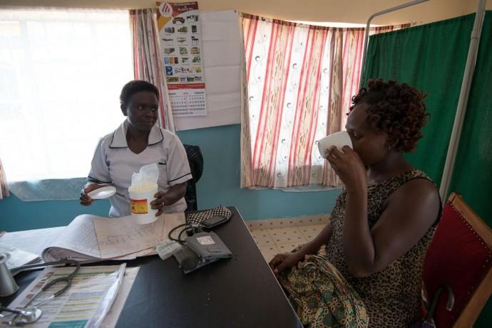 Nurse Agnes Nambuya gives Christine sulfadoxine-pyrimethamine drugs to prevent malaria in pregnancy. / Allan Gichigi, MCSP