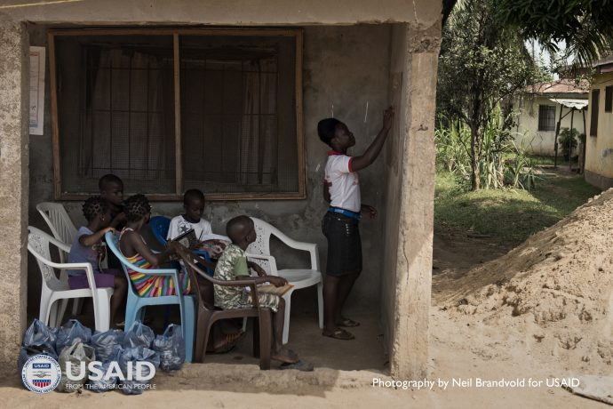 Aminata, 16, teaches her younger siblings while schools in Liberia were closed during the height of the Ebola epidemic / Neil Brandvold for USAID