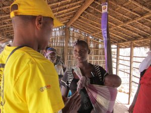 A community drug distributor provides a young mother with the appropriate dose of the trachoma-fighting drug Zithromax as part of a mass drug administration in Mozambique. / RTI International